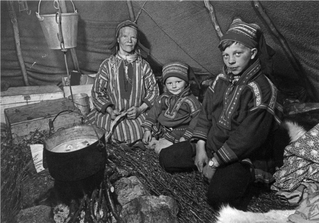 Interiør i et sametelt, tre personer sitter ved kokestedet, en gryte med mat henger over ilden. Finnmark.